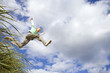 Boy (7-9 years) jumping from grass outdoors, low angle view