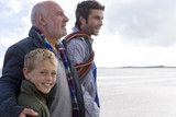 Boy (7-9 years) walking with grandfather and father on beach, smiling, side view