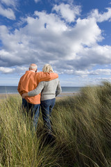 Senior couple arm in arm on sand dune, looking out to sea, rear view