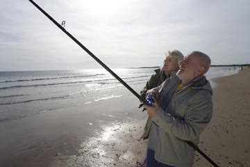 Senior couple on beach, man fishing, side view