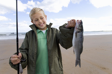 Boy (7-9) on beach with fishing rod and fish, smiling