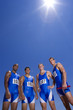 Male athletes, smiling, portrait, low angle view, (lens flare)