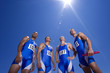 Group of male athletes, low angle view, (lens flare)