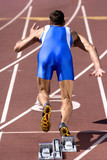 Male sprinter leaving starting block, rear view