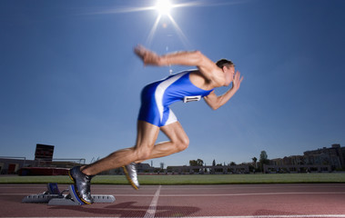 Male sprinter leaving starting block, side view (sun flare)