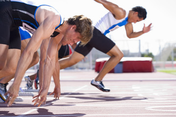 Male sprinters on starting blocks, side view