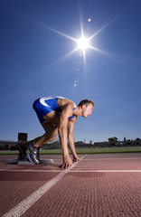 Male sprinter on starting block, side view (sun flare)