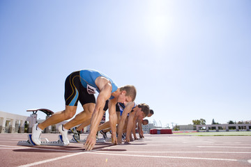 Male sprinters on starting blocks, low angle view (sun flare)