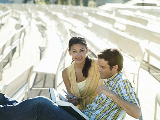 Young couple sitting in outdoor theatre, woman holding mobile phone, smiling, man reading book