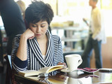 Young woman reading book at cafe table, focus on foreground