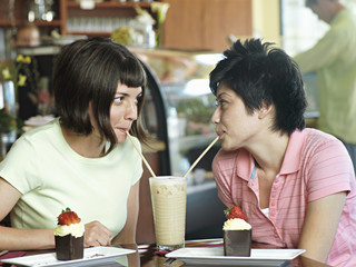 Two young women sitting at cafe table, sharing milkshake, drinking through straws, face to face