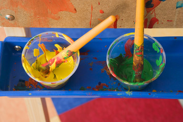 Multi-coloured paint pots in tray in nursery school classroom, close-up, overhead view (still life)