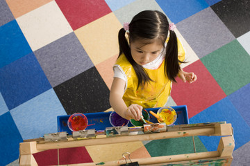 Girl (3-5) painting picture on easel in classroom, overhead view