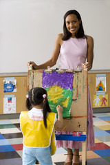 Girl (3-5) painting picture on easel in classroom, teacher looking on, smiling, portrait
