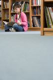 Girl (10-12) in spectacles sitting on floor beside bookshelf in library, reading book, surface level