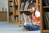Girl (10-12) sitting on floor beside bookshelf in library, reading book, smiling, side view, portrait