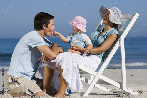 Family relaxing on beach, girl (2-3) sitting in mother's lap, feeding father, laughing, side view