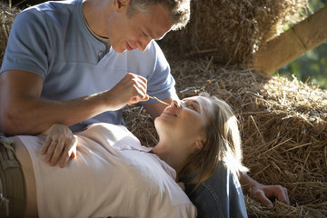 Couple relaxing on bales of hay in barn, man stroking woman with piece of straw