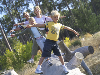 Two generation family walking in line on log, arms outstretched, smiling, front view (tilt)