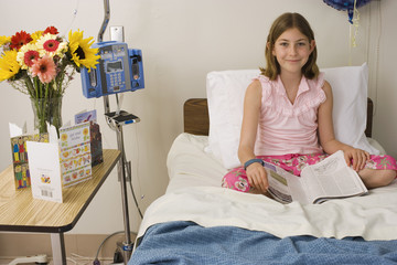 Girl (9-11) sitting in hospital bed, reading magazine, smiling, front view, portrait