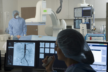 Doctors scanning patient in hospital, focus on woman looking at chest scan on visual monitor