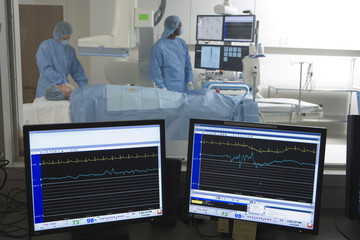 Doctors scanning patient in hospital, visual monitors in foreground