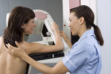 Patient having breast scan in hospital, nurse assisting, smiling, side view