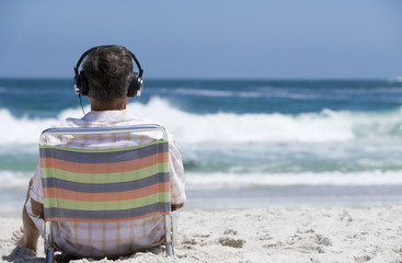 Senior man sitting on beach chair, wearing headphones, listening to personal stereo, rear view