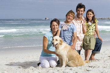 Two generation family kneeling on beach with dog, smiling, portrait, sea in background