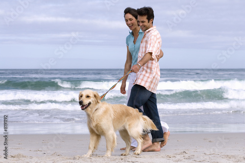 Couple walking dog on beach near water's edge, smiling, side view, sea in background