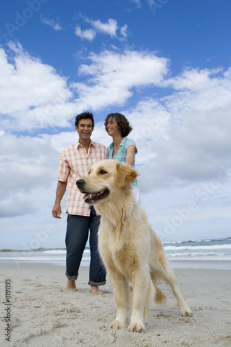 Couple walking dog on beach, smiling, surface level