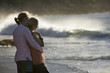 Affectionate teenage couple (17-19) standing on beach near surf, boy embracing girl, side view