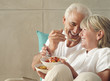 Senior couple relaxing on sofa at home, eating cereal, man feeding woman, smiling, side view