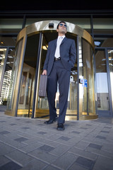 Businessman standing in front of revolving door, carrying briefcase, low angle view