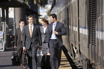 Four business colleagues walking along train station platform with luggage, smiling, front view