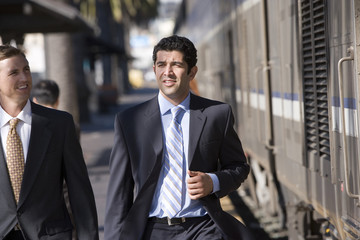 Two businessmen walking along train station platform, smiling, front view