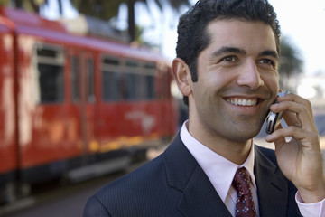 Businessman standing on train station platform, using mobile phone, smiling, close-up