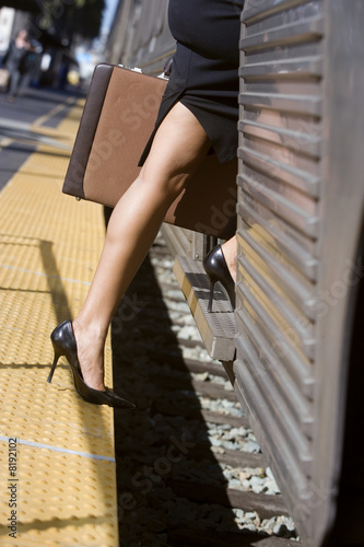 Businesswoman in skirt and high heels stepping on to train with briefcase, low section, side view