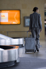 Businesswoman walking with luggage in airport baggage claim area, rear view
