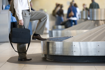 Businessman waiting for luggage in airport baggage claim area, side view, low section