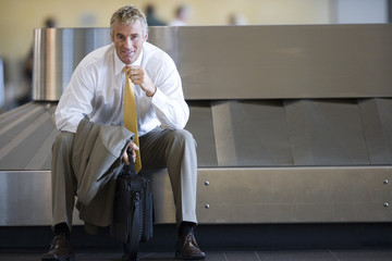 Businessman waiting for luggage in airport baggage claim area, smiling, front view, portrait