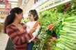 Mother and daughter (4-6) shopping in vegetable section of supermarket, woman holding carrots