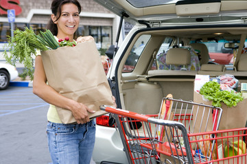 Woman loading car with grocery bags from trolley in supermarket car park, smiling, portrait
