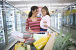 Mother and daughter (4-6) shopping in supermarket, woman pushing trolley in aisle, smiling