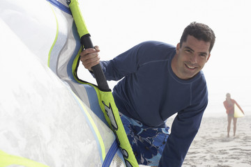Man in wetsuit holding windsurfing board on beach, smiling, portrait, woman in background