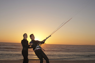 Young couple in wetsuits standing on beach at sunset, kiteboarding, side view