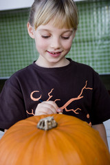 little girl carving a face in a Hallowe'en pumpkin