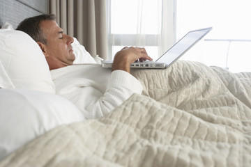 Businessman in bathrobe lying in hotel bed, using laptop, profile