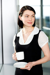 Businesswoman in office drinking a cup of coffee