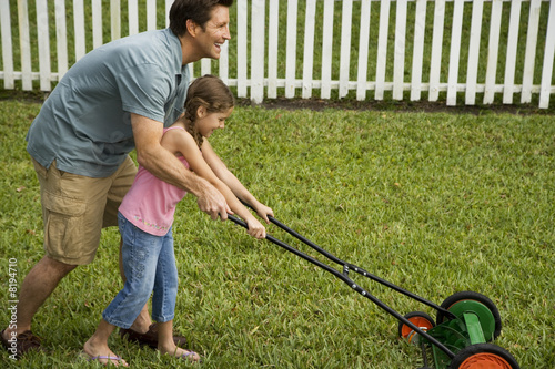 father and daughter mowing the lawn together\n